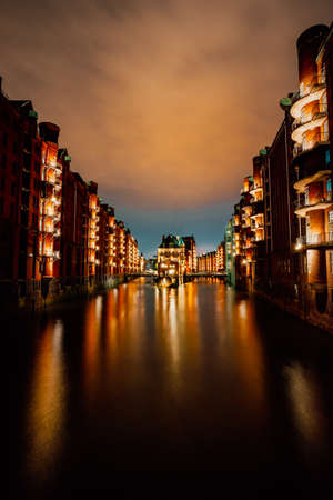 Hamburg, Germany. View of Wandrahmsfleet at dusk illumination light with reflection in the water. Located in Warehouse District - Speicherstadt Landmark of HafenCity quarter. 版權商用圖片