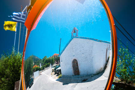 Reflection of small greek chapel in the traffic safety mirror. Stock Photo