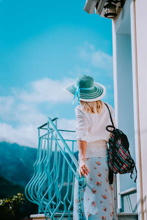 Young woman wearing summer clothes and straw hat going up stairs on sunny day. Vacation holidays in Europe Standard-Bild