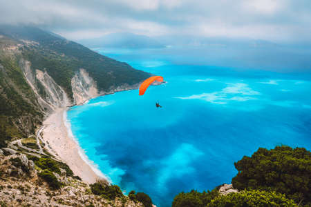 Aerial view of the paraglider flying over gorgeous Myrtos beach. Amazing water colors and beautiful coastline on kefalonia island, Greece.