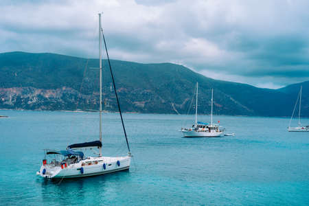 Yachts anchored near beautiful greek shoreline, on an overcast day in summer, coastal, travel, vacation concept