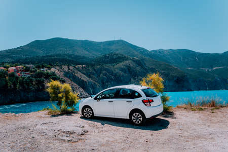 Vacation travel with car concept. Rental hired car in front of amazing bay with turquoise water. Discover Mediterranean Islands. Summer time holiday trip Banco de Imagens
