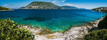 Panorama of crystal clear transparent blue turquoise teal Mediterranean seascape in Fiskardo town. Kefalonia, Ionian islands, Greece