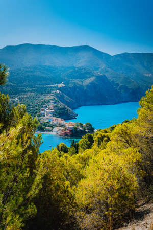 Top view to Assos village Kefalonia. Greece. Beautiful turquoise colored bay lagoon water surrounded by pine and cypress trees along the coastline