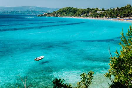 Pleasure white boat in crystal clear blue sea water. Spectacular Platis Gialos and Makris Gialos Beach, Kefalonia island near Lassi, Argostoli. Greece