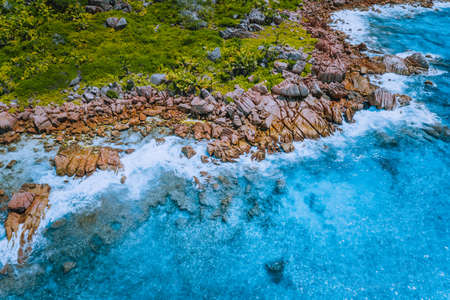 Aerial drone photo of Seychelles tropical hidden secret beach Marron at La Digue island. White sand beach with pure transparent turquoise ocean water and granite rocks