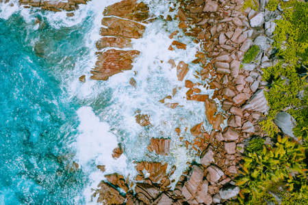 Aerial drone photo of Seychelles tropical beach Anse Cocos at La Digue Island. White rolling waves splash granite coastal rocks. Travel and vacation concept Stock Photo