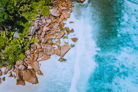 Seychelles La Digue Island. Aerial top view of ocean waves hitting huge bizarre granite rocks on the tropical beach anse cocos with turquoise azure water. Amazing rock cliff seascape in the coastline