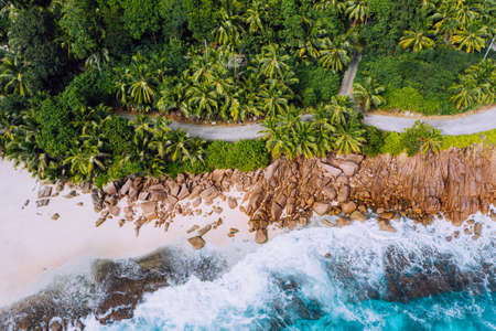 Seychelles Mahe island aerial drone landscape of coastline. Road along coastline of paradise sandy beach with palm trees and blue ocean waves rolling against granite rocks