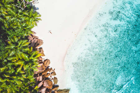 Aerial photo of exotic tropical white sand beach with young woman sunbathing relaxing. Concept of travel vacation holidays in paradise
