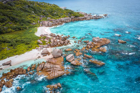 Aerial view of Seychelles tropical Marron beach at La Digue island. White sand beach with turquoise ocean water and quaint granite rocks. tropical paradise Stock Photo