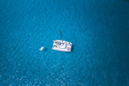 Aerial drone photo of catamaran boat at blue clear ocean water