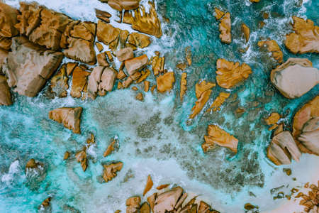 Aerial top view of tropical coastline. Bizarre granite rocks boulders, turquoise azure water. Amazing shore seascape Seychelles La Digue Island Stock Photo