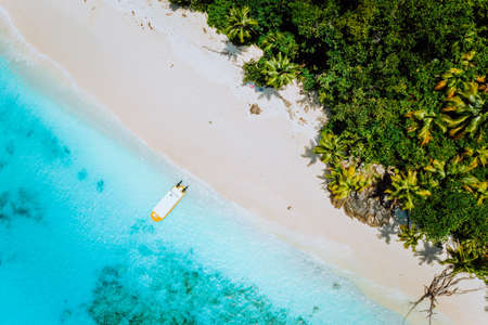 Aerial drone view of paradise beach with coconut trees and lonely tourist boat in turquoise shallow lagoon water