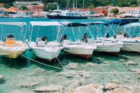 Summer scenery of port Fiskardo. Small day trip boats tied up to the pier. Picturesque outdoor scene of Kefalonia island, Greece, Europe. Traveling vacation concept Stock Photo