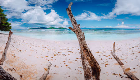 Impressive cloudscape above tropical island Praslin. Panorama of white sand paradise beach of anse Severe, La Digue, Seychelles