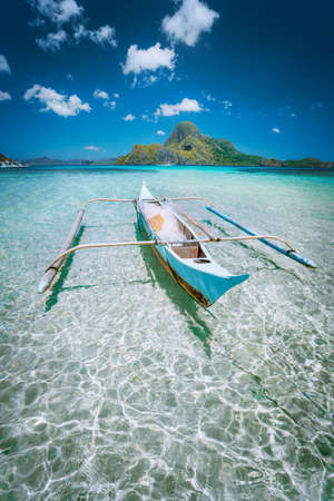 Traditional filippino fisher banca boat in blue lagoon at El Nido bay with Cadlao Island on Background. Palawan Island, Philippines