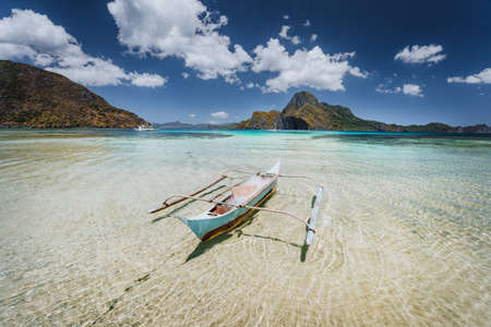 Traditional filippino fishermen banca boat in blue tropical lagoon at El Nido bay with Cadlao Island on Background. Palawan Island, Philippines Stock Photo