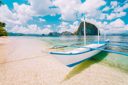 White banca island hopping boat at Las cabanas beach with amazing Pinagbuyutan island in background. Beautiful landscape scenery in El Nido, Palawan, Philippines