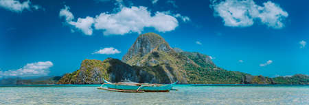 El Nido, fishermens boat in blue bay with panoramic view of Cadlao Island in background, Palawan, Philippines Stock Photo