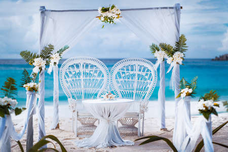 Beach wedding arch gazebo ceremonial decorated with white flowers on a tropical grand anse sand beach. Outdoor beach wedding setup. La Digue, Seychelles Stock Photo - 123541361
