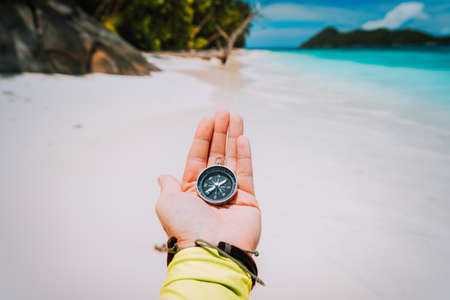 Hand with compass against tropical sandy beach and ocean. POV Travel concept Stock Photo