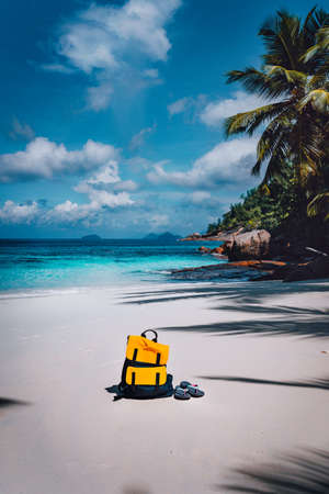 Traveler yellow backpack and flip flops on the sandy tropical beach on summer holidays trip, travel background with copy space.