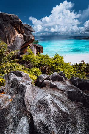 Natural viewpoint to beautiful impressive Grand Anse beach on La Digue island in Seychelles. Amazing white clouds above ocean horizon.