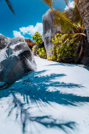 Walking pathway along the beach between giant granite boulders on Anse Source D Argent, La Digue island Seychelles. Contrast shadow of palm leaves on the ground. Vacation travel concept.