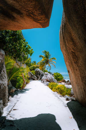 Walking path through giant bizarre granite rock boulders at the famous Anse Source dArgent beach on island La Digue in Seychelles. Exotic paradise scenery travel concept shot.