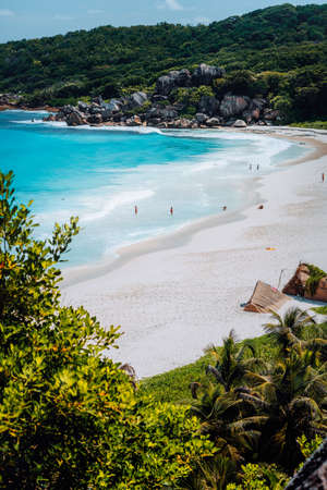 Beautiful Grand Anse beach with unrecognizable tourist people on La Digue island in Seychelles. Vertical shot.