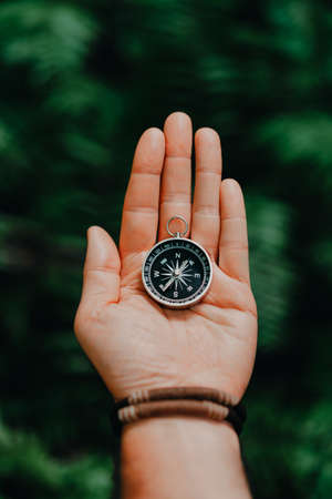 Hand with compass against tropical forest jungle terrain. POV Travel concept. Stock Photo