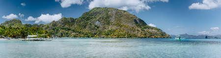 Vue panoramique sur la baie d'El Nido par une journée ensoleillée tranquille. Littoral pittoresque avec palmiers, plage de sable et eau claire. Nature unique de Palawan, Philippines