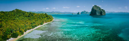 Panoramic drone aerial view of coastal scenery from the mainland Palawan with tropical Pinagbuyutan islands on horizon. El Nido-Philippines. Best natural wonder in Southeast Asia Bacuit archipelago