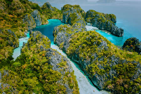 공중 무인 항공기는 들쭉날쭉한 석회암 카르스트 절벽으로 둘러싸인 카약을 타고 관광객이 내부를 탐험한 아름다운 얕은 열대 크고 작은 라군을 봅니다. 엘니도, 팔라완 필리핀