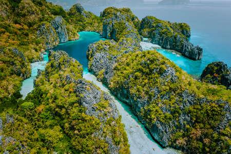 Vista aerea del drone bella laguna tropicale poco profonda, grande e piccola, esplorata all'interno da turisti su kayak circondati da scogliere carsiche calcaree frastagliate El Nido, Palawan Filippine