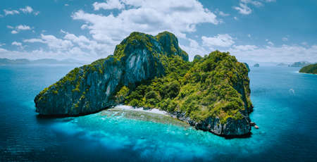 Aerial drone panorama picture of tropical paradise epic Entalula Island. Karst limestone rocky mountains surrounds the blue lagoon with beautiful coral reef