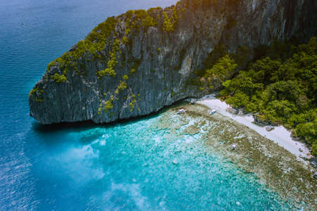 Aerial drone view of tropical beach with banca boats on Entalula Island. Karst limestone rocky mountains surrouns blue bay with beautiful coral reef