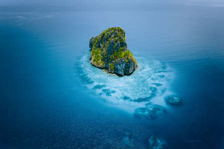 Aerial drone view of a beautiful secluded cliff island surrounded by azure turquoise blue ocean water. Bacuit archipelago is one of the best places for diving. El Nido, Palawan Stock Photo
