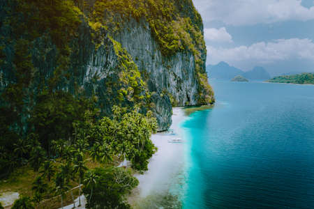 El Nido, Palawan, Philippines. Aerial drone view of tourist boats arriving tropical Ipil beach on Pinagbuyutan Island. Idyllic remote location with turquoise blue ocean water and palm trees