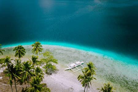 El Nido, Palawan, Philippines. Aerial drone view of tourist island hopping boats moored at tropical Ipil beach on Pinagbuyutan Island