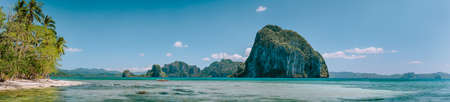 Tropical panorama scenery of coastline with huge rocky island on the background. National Marine Park El Nido, Palawan, Philippines Stock Photo
