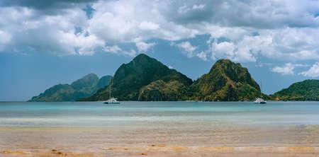 Panoramic scenery from Corong Corong Beach, El Nido, Palawan, Philippines. Landscape of mountain coastline, bay and yacht boat at anchor