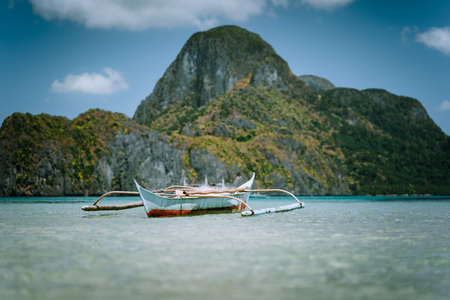 Traditional filippino banca boat in blue tropical lagoon at El Nido bay. Impressive karst mountains of Cadlao Island in blurred Background. Palawan Island, Philippines