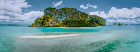 Palawan, Philippines. Aerial drone panoramic view of sandbar with lonely tourist boat in turquoise coastal shallow waters and coral reef in El Nido archipelago