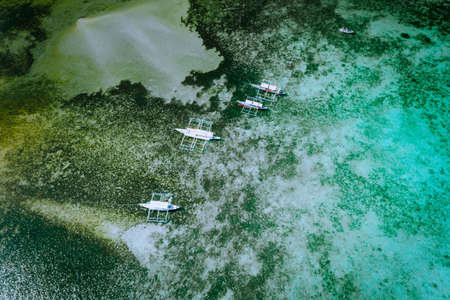 Aerial drone top down view of local banca boats and coral reef in shallow transparent lagoon water El Nido. Bacuit archipelago. Palawan, Philippines