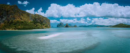 Palawan, Philippines. Aerial panoramic scenic picture of sandbar with lonely tourist boat in turquoise coastal water and cloudscape. El Nido Bacuit archipelago. Many limestone Island in background