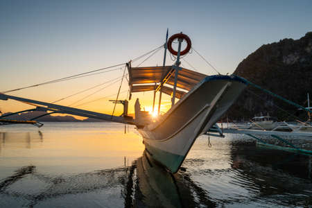Tropical harbor bay in evening. Golden hour in lagoon in Philippines, Palawan, El Nido. Sunset on beach. Tranquil scenic sundown above mountains islands on horizon Stok Fotoğraf