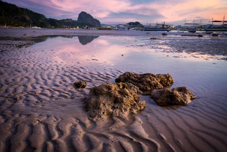 Blue hour at tropical harbor bay in evening. Tranquil sunset in lagoon shallow water and sandy beach in Philippines, Palawan, El Nido. Sundown on beach. Scenic view with mountains isles on horizon