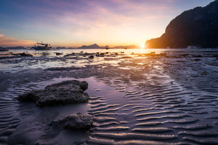 Tropical beach in ebb time low tide on sunset. Mudflats and sun reflections at the golden hour. mountain chain isles at horizon. Coron Corong beach, El Nido, Phillipines